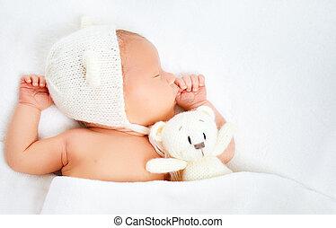 Cute newborn baby in bear hat sleeps with toy teddy bear