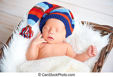 Cute newborn baby in blue knit cap sleeping in basket