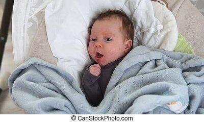 Cute newborn baby in crib - Cute sleepy newborn baby yawning...