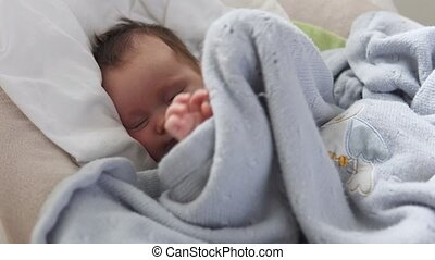 Cute newborn baby in crib - Mother's hand tenderly stroking...