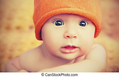cute newborn baby in knitted orange hat cap