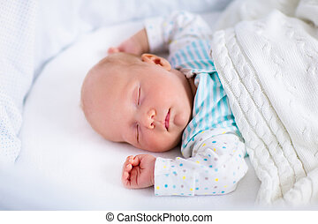 Cute newborn baby in white bed