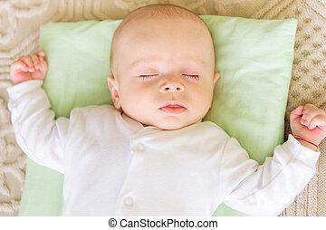 Cute newborn baby sleeping in bed