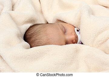 Cute newborn baby sleeping in soft blanket
