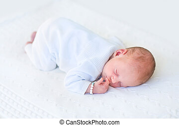 Cute newborn baby sleeping on his tummy on a white knitted blank