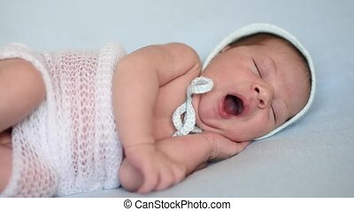 cute newborn baby yawns - newborn baby yawns lying on a blue...