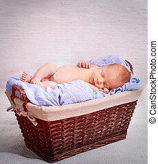 newborn boy sleeping in a basket