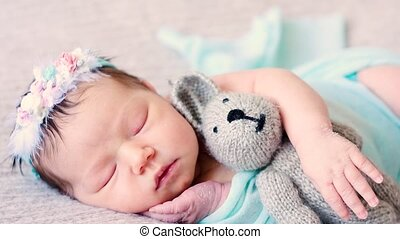 Cute newborn little baby lies on bed with favorite plush toy...