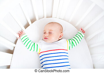 Cute newborn little boy sleeping in a white round crib
