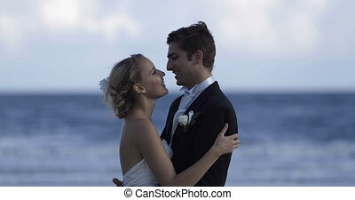 Cute newlywed couple embracing at the beach on their wedding day