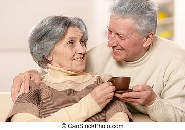 Cute old couple drinking coffee at home