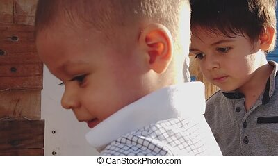 Cute older brother feeling sad when baby doesnt want to let him to play with his toys. Close up outdoors