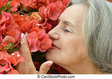 cute older woman - Happy cute older woman with pink flowers