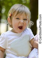Cute one year old baby girl yawning