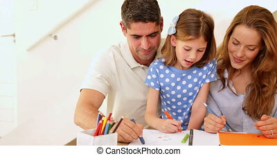 Cute parents and daughter colouring together at home in living room