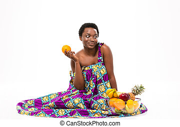Cute pensive african american woman sitting and holding orange