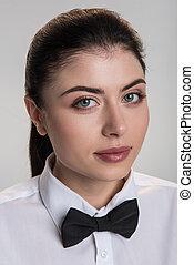 Cute pensive woman posing in bow tie