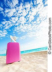 Cute pink baggage bag on the beach