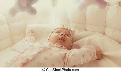 Cute playful baby girl in her cot - Newborn baby girl in her...