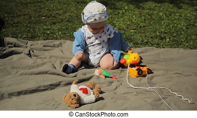 Cute playful smiled blond 1 years old boy sitting on green grass outdoor playing with toys