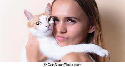 Cute portrait of a girl with a cat. On a light background.