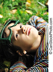 Cute positive boy with glasses laying on green grass ground and looking up