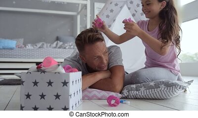 Cute positive girl putting hair curlers on her fathers hair...