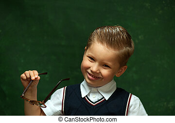 Cute positive little boy with glasses is smiling