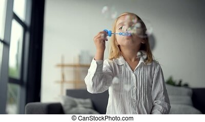 Cute positive little girl blowing soap bubbles