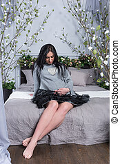 Cute pregnant brunette woman in a dress keeping hand on belly while sitting on the bed