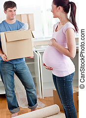 cute pregnant wife looking at her husband holding box standing in their new kitchen during removal