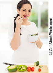 cute pregnant woman eating salad