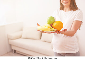 Cute pregnant woman is caring of her health