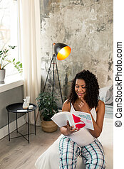 Cute pregnant woman reading a book in her room.