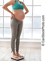 Cute pregnant woman standing on scale in her room