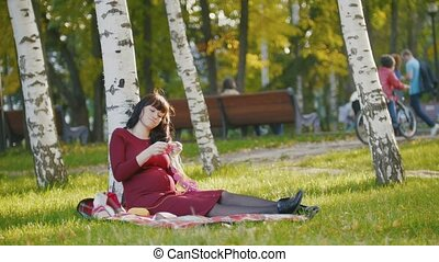 Cute pregnant woman with belly in autumn park make hobby knitting needles
