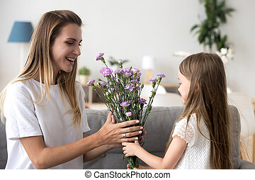 Cute preschool daughter giving to mother flowers
