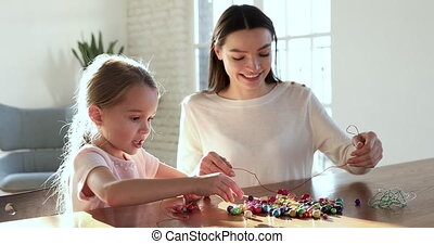 Cute preschool daughter making necklace with young mom babysitter