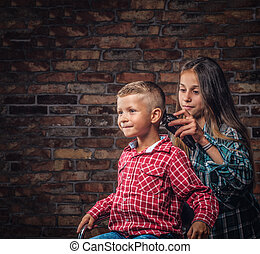 007493a678ac1 Cute preschooler boy getting haircut. The older sister cuts her little  brother with a trimmer