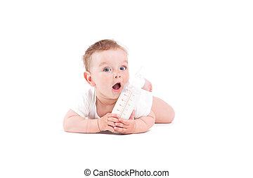 cute pretty baby boy in white shirt lies on tummy with milk bott