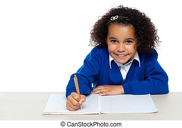 Cute primary kid writing her assignment - Studio shot of a...
