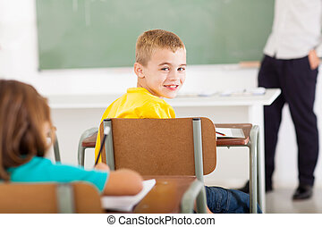 primary school student looking back in classroom