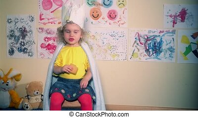 Cute princess girl with paper crown sitting and eating...
