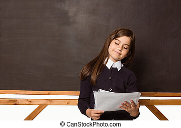 Cute pupil holding white pages in classroom