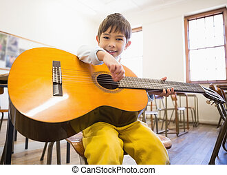 Cute pupil playing guitar in classroom at the elementary ...