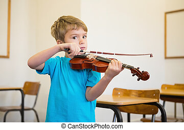 Cute pupil playing violin in classroom at the elementary...