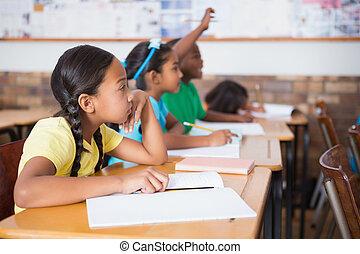 Cute pupil raising hand in classroom