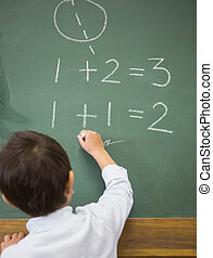 Cute pupil writing maths on chalkboard at the elementary...