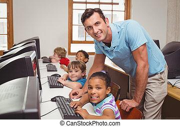 Cute pupils in computer class with teacher