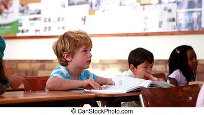 Cute pupils listening attentively in classroom in elementary...
